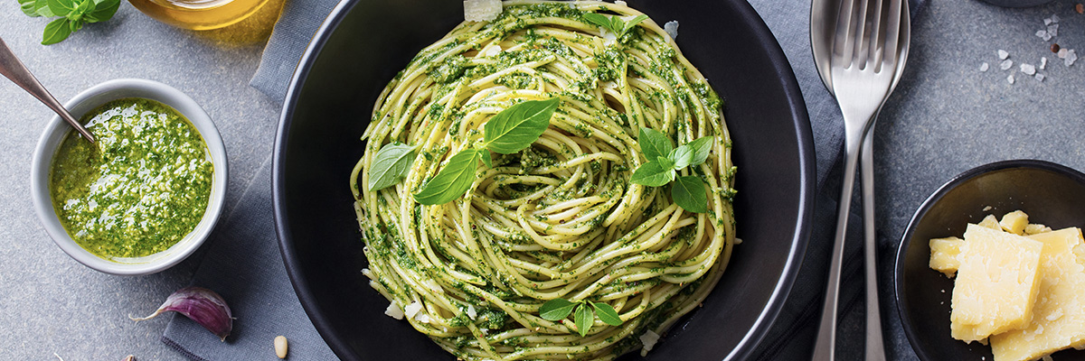 Vihreä pestopasta mustalla lautasella