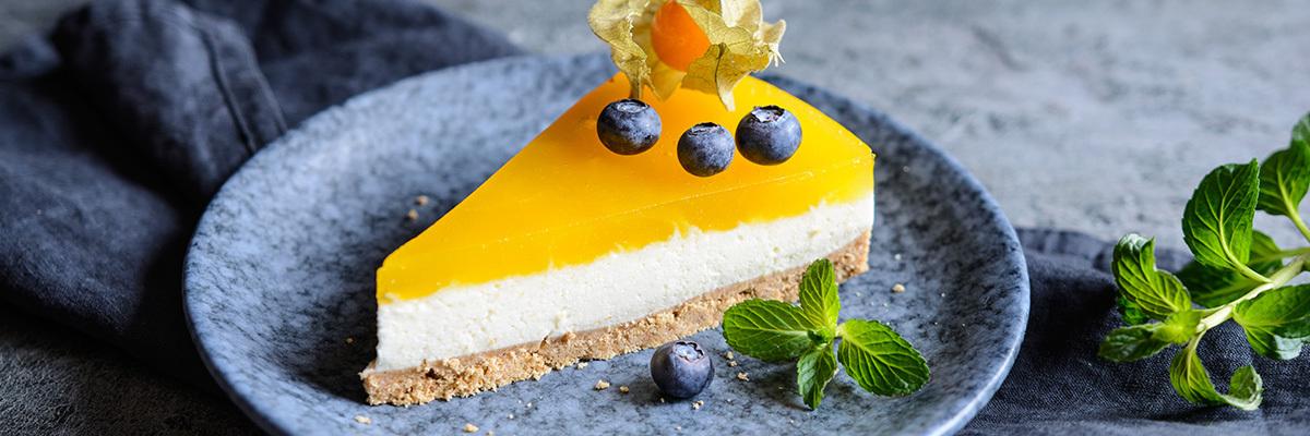 Mangojuustokakkupala sinisellä lautasella
