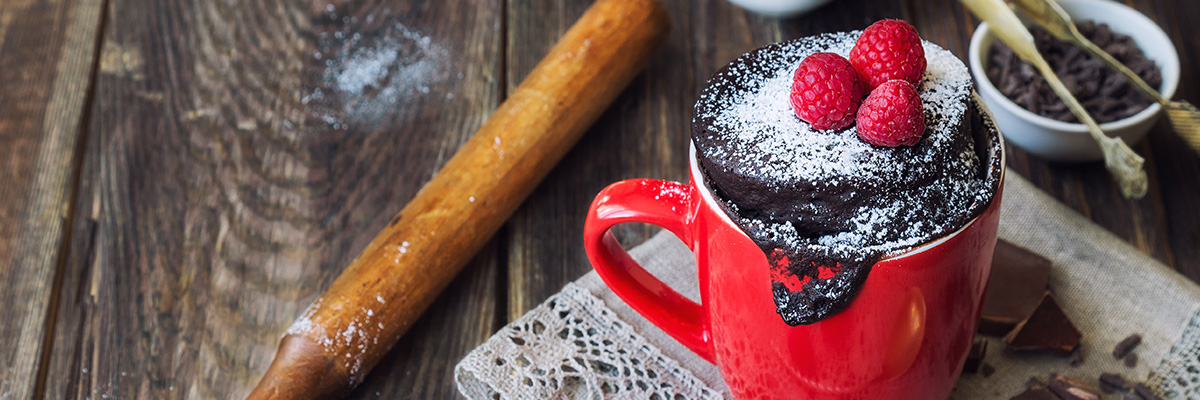 Vadelmilla ja tomusokerilla koristeltu mikrobrownie punaisessa mukissa rustiikkisella taustalla, helppoa ja nopeaa leivottavaa, mikrobrownie