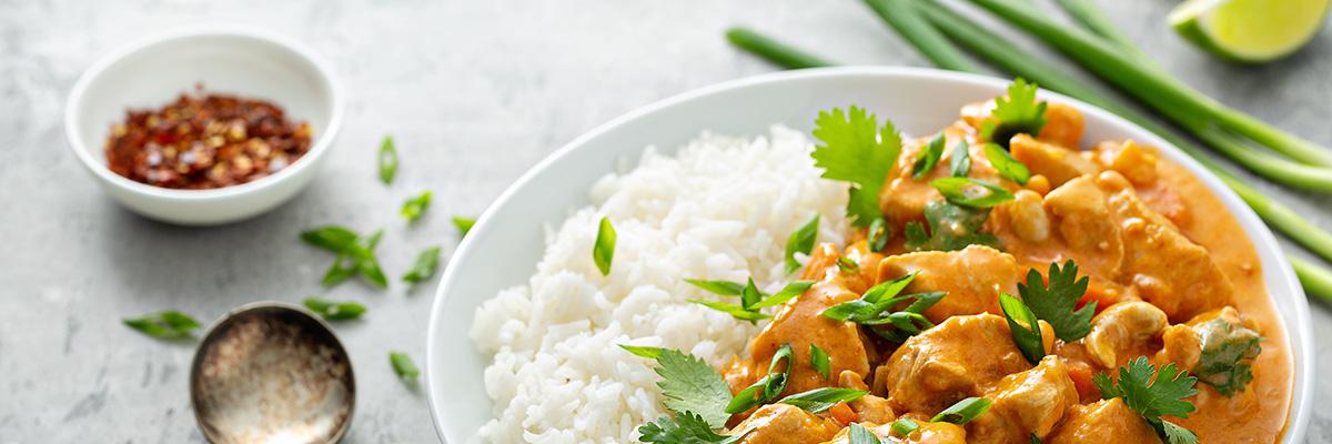 kanakastike yrttien ja riisin kanssa valkoisella lautasella, helppo ruoka kahdelle