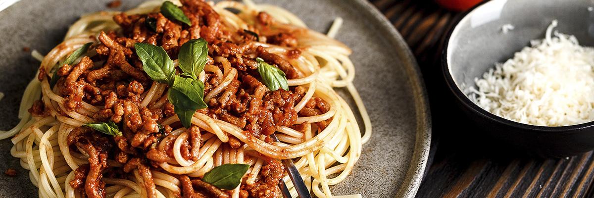 Soijabolognese basilikalla ja parmesaanilla harmaalla lautasella