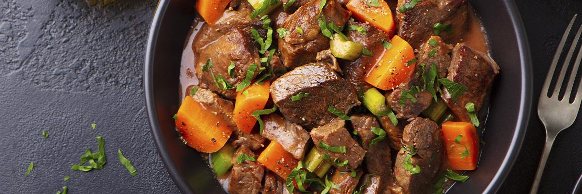 Lihapata porkkanoilla ja juureksilla tummalla taustalla