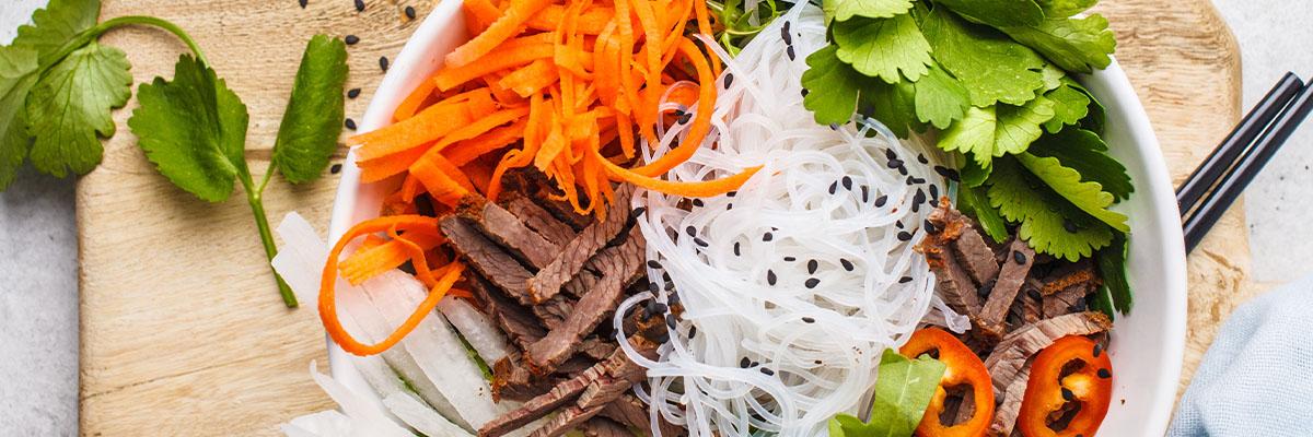 Yrteillä koristeltu vietnamilainen riisinuudelisalaatti naudanlihalla ja kasviksilla valkoisessa kulhossa ylhäältä kuvattuna, yrtit