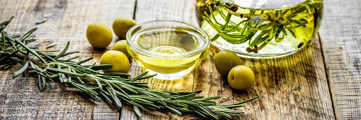 Yrttejä ja oliiviöljyä puisella pöydällä