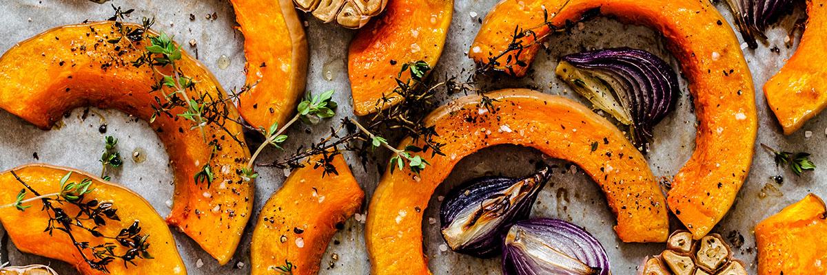 Lähikuva paahdetuista sipuleista ja yrteillä maustetuista paahdetuista myskikurpitsasiivuista