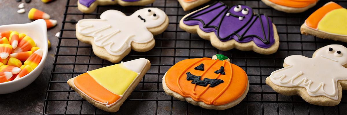 haamujen, lepakoiden ja kurpitsojen muotoisia värikkäitä halloween keksejä metalliritilällä tummalla taustalla